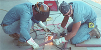 Two workers cutting and welding metal rods. Workers can be seen wearing gloves and eye protection. By NIOSH.